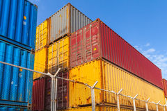 Colorful cargo containers are stacked behind metal fence Stock Photo