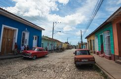 Colorful Caribbean aged village with cobblestone street, classic red car and Colonial house, Trinidad, Cuba, America. Colorful Colonial ancient village classic stock photos