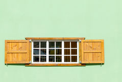 Colorful Caribbean Window and Shutters in a Green Wall Stock Images