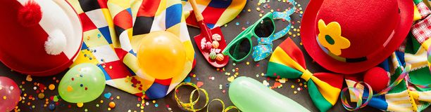 Colorful carnival banner with party accessories. Including hats, glasses, balloons, streamers and bow ties in a full frame view Stock Images