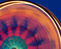 Colorful Carnival Ferris Wheel. A Colorful Carnival Ferris Wheel creates a beautiful blur of colors as it spins against the dusk sky Stock Photos