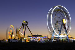 Colorful carnival Ferris wheel and gondola spinning in motion blurred at twilight Stock Photos