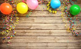 Colorful carnival or party frame of balloons, streamers and confetti on rustic wooden board. Colorful carnival or party frame of balloons, streamers and confetti stock images