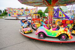 Colorful carousel at luna park. Colorful carousel with different vehicles and sitting child on a luna park in Poznan, Poland Stock Image