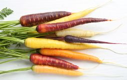 Carrots. Colorful carrots on a wooden white background Royalty Free Stock Photo