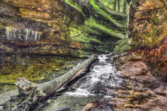 Colorful Cascade at Turkey Run. Water cascades over colorful sandstone from a narrow passage with green rocky walls In Indiana's Turkey Run State Park Stock Photo