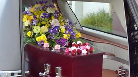 A colorful casket in a hearse or chapel before funeral or burial at cemetery. Closeup shot of a colorful casket in a hearse or chapel before funeral or burial at stock footage