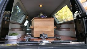 Colorful casket in a hearse or chapel before funeral or burial at cemetery. Closeup shot of a colorful casket in a hearse or chapel before funeral or burial at Royalty Free Stock Image
