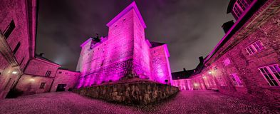 Colorful castle illumination at night. Medieval castle exterior night scene during light festival. Surreal view with very colorful and vibrant illumination stock image