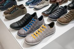 Colorful casual shoes on white shelves. At store Stock Photo
