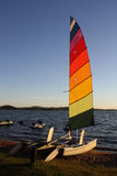 Colorful Catamaran on Lake Beach. Catamaran with rainbow sail sitting on a lake beach in late afternoon light Stock Images