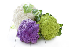 Colorful Cauliflower. Three colorful Cauliflower cabbages on white wooden board stock images