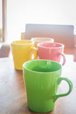 Colorful ceramic coffee cups on wooden table Royalty Free Stock Image