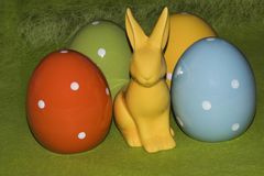 Colorful easter eggs and an Easter bunny in front of a green background. Colorful ceramic easter eggs and an Easter bunny in front of a green background royalty free stock image