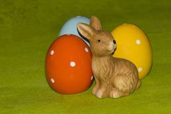 Colorful easter eggs and an Easter bunny in front of a green background. Colorful ceramic easter eggs and an Easter bunny in front of a green background royalty free stock images
