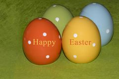 Colorful ceramic easter eggs in front of a green background. Four colorful ceramic easter eggs in front of a green background with Easter greetings in English stock photography