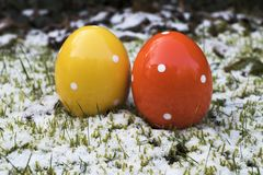 Colorful ceramic easter eggs which are standing in grass and snow. Wintry Easter with colorful ceramic easter eggs which are standing in grass and snow stock photography
