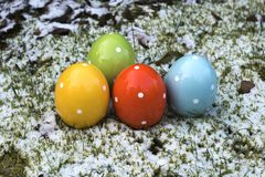 Colorful ceramic easter eggs which are standing in grass and snow. Wintry Easter with colorful ceramic easter eggs which are standing in grass and snow royalty free stock photo