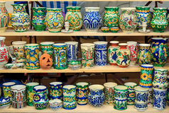 Colorful ceramic jugs on the shelf Stock Images