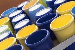 Colorful ceramic pots in market, sunny day. Colorful ceramic pots in market, collection of flowerpots, blue and yellow Stock Images