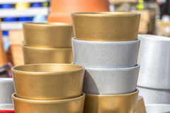 Colorful ceramic pots in market, sunny day. Colorful ceramic silver and golden pots in market, collection of flowerpots Royalty Free Stock Images