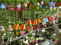 Colorful ceramic wind chimes with natural environment in organic orchid farm with small plants and cartoon decoration. stock images