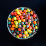 Colorful cereal. Colorful breakfast cereal in a blue bowl, shot from above with pure black background Royalty Free Stock Photography