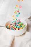 Colorful cereal falling on a bowl on a white background Stock Photos