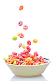 Colorful cereal falling on a white bowl royalty free stock photo