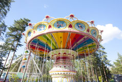 Colorful chain swing carousel in motion at amusement park on blue sky background. Stock Image