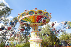 Colorful chain swing carousel in motion at amusement park on blue sky background. Royalty Free Stock Images
