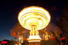 Colorful chain swing carousel in motion at amusement park at night. Stock Photo