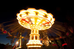 Colorful chain swing carousel in motion at amusement park at night. Colorful chain swing carousel in motion at amusement park at night Stock Photography