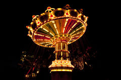 Colorful chain swing carousel in motion at amusement park at night. Stock Photos