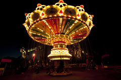Colorful chain swing carousel in motion at amusement park at night. Stock Photography