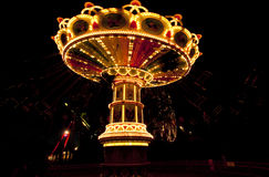 Colorful chain swing carousel in motion at amusement park at night. Stock Image