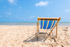 Colorful chair on sandy beach on sunny day looking for the blue Stock Photo