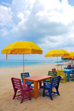 Colorful chair and table with yellow umbrella on the beach Royalty Free Stock Photo