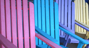 Colorful Chairs. Brightly painted adirondack style chairs create a concept for outdoor furniture, or an invitation to relaxation, a party or vacation Stock Photos