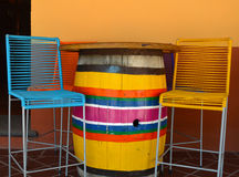 Colorful chairs and barrel table on mexican plaza. Colorful chairs and barrel table Stock Photos
