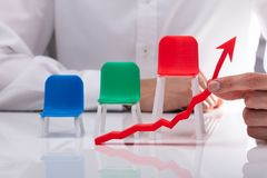 Chairs Behind Businessman Showing Arrow In Upward Direction. Colorful Chairs Behind Businessman`s Hand Showing Red Arrow In Upward Direction On Desk stock photography