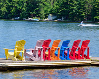 Colorful chairs on a dock. And a jet skiier in the distance Stock Photo