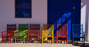 Colorful Chairs. A row of colorful chairs in front of a simple entryway at the Pisac market in Peru Stock Photo