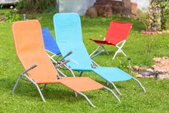 Colorful chairs standing on a lawn in the garden for a rest. royalty free stock photos