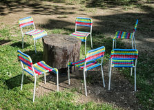 Colorful chairs and wooden table on the lawn Royalty Free Stock Image