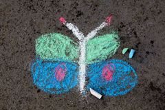 Chalk drawing on asphalt: beautiful butterfly. Colorful chalk drawing on asphalt: beautiful butterfly royalty free stock photo