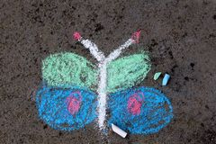 Colorful chalk drawing: beautiful butterfly. Colorful chalk drawing on asphalt: beautiful butterfly royalty free stock photo