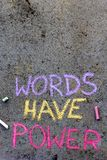 Chalk drawing: text WORDS HAVE POWER. Colorful chalk drawing on asphalt: text WORDS HAVE POWER stock photos