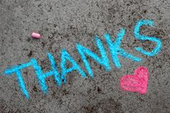 Chalk drawing: words THANKS and small heart. Colorful chalk drawing on asphalt: words THANKS and small heart royalty free stock images