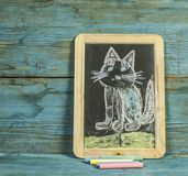 Colorful hand drawing with chalk on blackboard : funny cat. Colorful chalk drawing on blackboard : funny cat hand royalty free stock photography